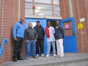 Larry Bailey, Pedro Ortega, Ben Hines, Jose Daniels, and Wendell Gilmore stand guard in front of Sankofa Academy.