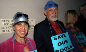 people with swim caps and goggles at city council meeting
