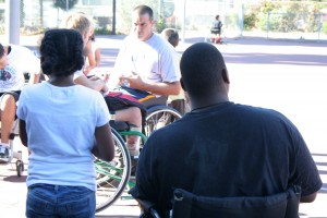 Solomon Tyson (right) and his niece Leilani (left) look on as head coach of the Bay Cruisers Varsity wheelchair basketball team, Trooper Johnson, talks to some of the players.