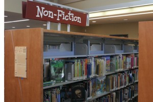 Stacks of non-fiction books are marked with a kid-friendly font in the 81st Avenue Library. Neighborhood kids and students will also have access to children's librarian Derrick DeMay.