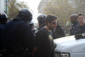 Police restrain a man on Franklin and 14th Street; his face is bleeding from hitting the ground when police restrained him. Photo by Brittany Schell.