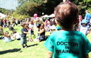 A boy wearing a doctor's costume observes people during the 100th anniversary of Children's Hospital at Fairyland.