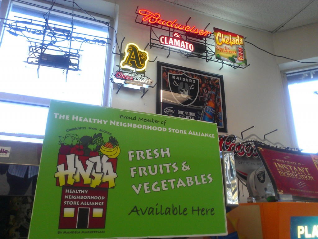 A Healthy Neighborhood Stores Alliance banner hangs in Bottles Liquor store in West Oakland, indicating the store has pesticide-free produce for sale.