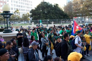 A crowd of Oakland fans gather beside the fence in Frank Ogawa Plaza.