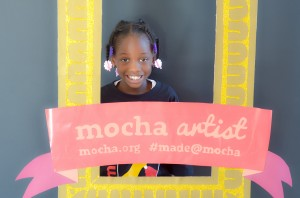 "Meley Portlock, 6, poses behind the ""MOCHA Artist"" frame during the Museum of Children's Arts open house."