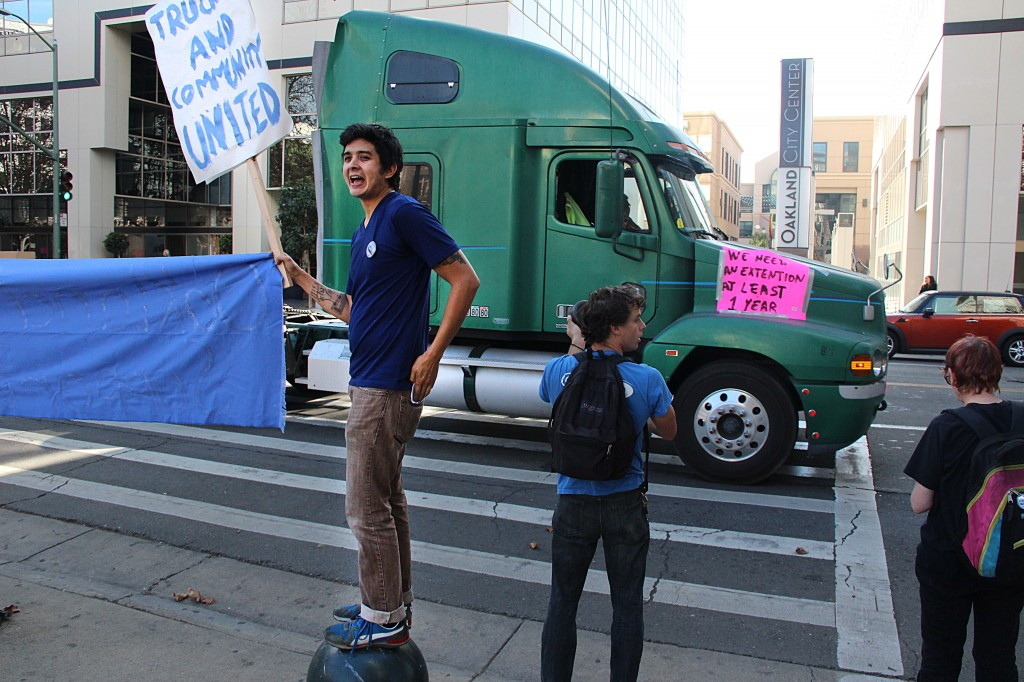 An activist brandishes a picket in front of a passing tractor-trailer.