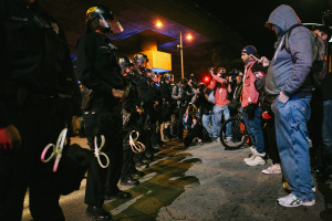 Protesters confront a police barricade at the intersection of MacArthur Blvd and Grand Ave in Oakland. November 24, 2014. (Photo by Bonnie Chan)