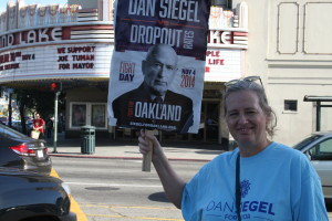 Natasha Dean pickets outside Grand Lake Theater, which displays support for mayoral candidate Joe Tuman. Photo by Joshua Escobar.