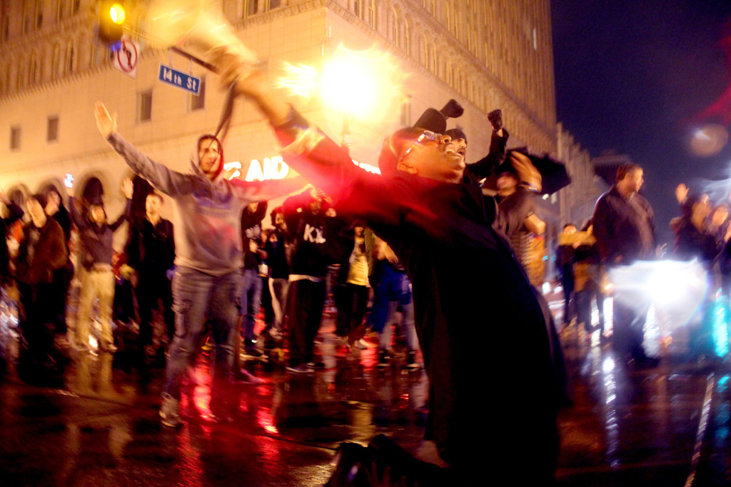 """At the intersection of 14th and Broadway, protestors chanted """"Hands up, don't shoot."""""""