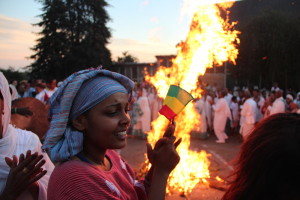 A woman holds on to her Ethiopian flag as the crowd dances around the Demara.