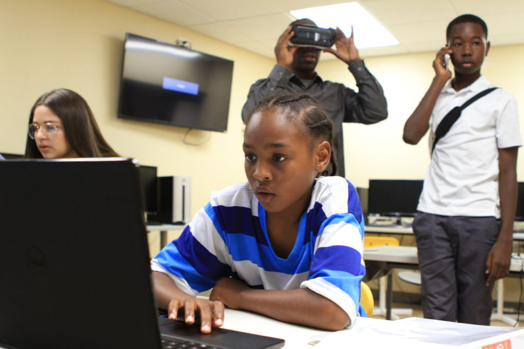 Xavier Stroud, 10, of East Oakland uses 3D technology gaming software at the David E. Glover Education and Technology Center. Youth Program Director, Paul Williams, exhibits a VR game in the background. Credit: Stefanie Le.
