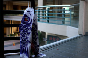 A carp streamer leaning to the railings outside of a Japanese restaurant. Photo by Tian Chenwei.