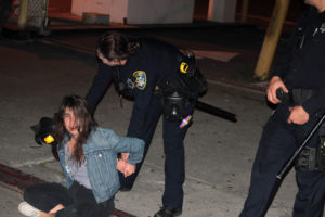 OPD officers arrest a protester in downtown Oakland. Photo by Andrew Beale.