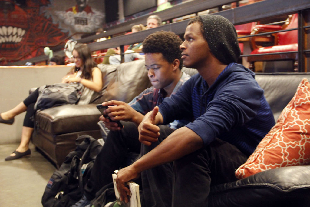 High school student Steven Beard, left, and his friend watch results on one of The New Parkway's theaters. Photo by Ryan Lindsay.