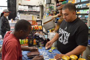 Said Hassan, cashier at Telegraph Quality Market, charges a customer purchasing flavored cigarettes on Thursday, Sept. 22, 2017, in Oakland, California. The prohibition of sales of flavored tobacco products that will take effect in 2018 will impact the store owned by his family directly.