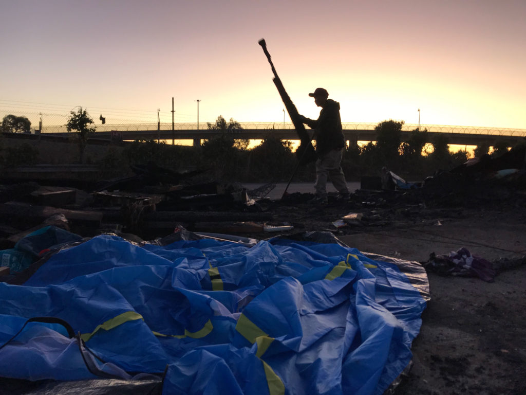 A resident of the East 12th Street homeless encampment clears debris following a fire. Photo by Julia Kane.